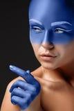 Il ritratto di una donna che sta posando ha coperto  Immagine Stock
