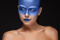 Il ritratto di una donna che sta posando ha coperto di pittura blu Immagine Stock Libera da Diritti