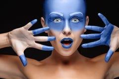Il ritratto di una donna che sta posando ha coperto di pittura blu Fotografie Stock