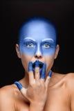 Il ritratto di una donna che sta posando ha coperto di pittura blu Fotografie Stock Libere da Diritti