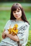 Il ritratto di una donna con giallo lascia in un parco di autunno Fotografie Stock