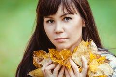 Il ritratto di una donna con giallo lascia in un parco di autunno Immagini Stock