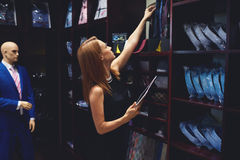 Il ritratto di una donna di affari controlla la disponibilità delle merci utilizzando il cuscinetto di tocco mentre sta nel suo n Fotografia Stock
