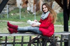 Il ritratto di una donna ha vestito nel rosso con un gatto in lei le armi Immagini Stock