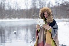Il ritratto di una donna di viaggio nell'inverno copre la condizione davanti al lago della foresta dell'inverno con una mappa nel Fotografia Stock Libera da Diritti