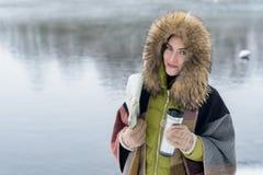 Il ritratto di una donna di viaggio nell'inverno copre la condizione davanti al lago della foresta dell'inverno con una mappa nel Immagini Stock