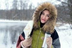 Il ritratto di una donna di viaggio nell'inverno copre la condizione davanti al lago della foresta dell'inverno con una mappa nel Fotografie Stock