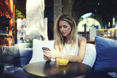 Il ritratto di una femmina bionda sveglia ha letto qualcosa sul suo Smart Phone mentre si sedeva nella caffetteria moderna Fotografia Stock
