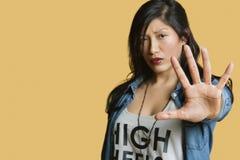 Il ritratto di una giovane donna che gesturing la fermata cede firmando un documento il fondo colorato immagini stock