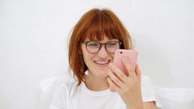 Il ritratto di una ragazza con un telefono, trova la vostra aria favorita in uno Smart Phone sorridente, ascolta tramite le cuffi video d archivio