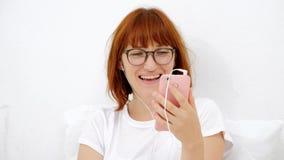 Il ritratto di una ragazza con un telefono, trova la vostra aria favorita in uno Smart Phone sorridente, ascolta tramite le cuffi archivi video