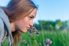 Il ritratto di una ragazza odora un wildflower fragrante fotografia stock