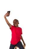 Il ritratto di una scuola ha invecchiato il ragazzo con un telefono cellulare Fotografie Stock Libere da Diritti