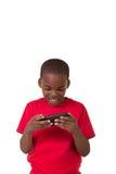 Il ritratto di una scuola ha invecchiato il ragazzo con un telefono cellulare Immagine Stock
