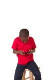 Il ritratto di una scuola ha invecchiato il ragazzo con un telefono cellulare Immagini Stock