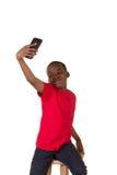 Il ritratto di una scuola ha invecchiato il ragazzo con un telefono cellulare Fotografia Stock Libera da Diritti
