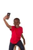 Il ritratto di una scuola ha invecchiato il ragazzo con un telefono cellulare Fotografie Stock