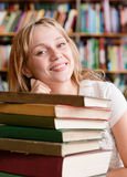 Il ritratto di una studentessa con il mucchio prenota in biblioteca Immagini Stock Libere da Diritti