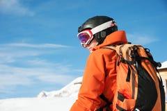 Il ritratto di uno sciatore in un'arancia complessiva con uno zaino sul suo indietro in un casco sta contro lo sfondo della a Immagine Stock