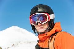 Il ritratto di uno sciatore in un'arancia complessiva con uno zaino sul suo indietro in un casco sta contro lo sfondo della a Immagine Stock Libera da Diritti