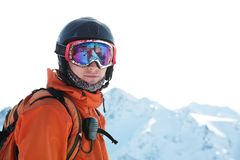 Il ritratto di uno sciatore in un'arancia complessiva con uno zaino sul suo indietro in un casco sta contro lo sfondo della a Immagini Stock
