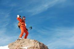 Il ritratto di uno sciatore in un'arancia complessiva con uno zaino sulla sua parte posteriore e gli sci sulle sue spalle in un c Immagini Stock