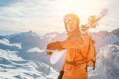 Il ritratto di uno sciatore in un'arancia complessiva con uno zaino sulla sua parte posteriore e gli sci sulle sue spalle in un c Fotografie Stock