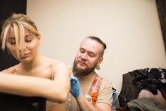 Il ritratto di uno stregone del tatuaggio dell'uomo mostra il processo di creare un tatuaggio Fotografia Stock