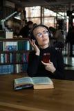 Il ritratto di uno studente di college che studia e gode della musica d'ascolto in biblioteca con cuffie Fotografia Stock