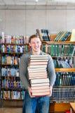 Il ritratto di uno studente maschio con il mucchio prenota nella biblioteca di istituto universitario Immagine Stock Libera da Diritti