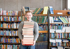 Il ritratto di uno studente maschio con il mucchio prenota nella biblioteca di istituto universitario Fotografie Stock