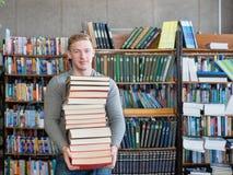 Il ritratto di uno studente maschio con il mucchio prenota nella biblioteca di istituto universitario Fotografia Stock Libera da Diritti