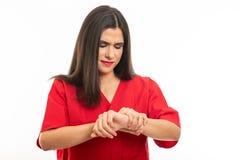 Il ritratto di uso dell'infermiere sfrega la fabbricazione del gesto di dolore del polso immagini stock