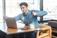 Il ritratto di vista di Sde di giovane uomo d'affari infelice aggressivo in camicia delle blue jeans sta sedendo in caffè ed aven fotografia stock libera da diritti