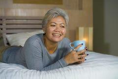 Il ritratto domestico della donna americana asiatica matura attraente e riuscita con capelli grigi che si siedono sul caff? beven fotografia stock libera da diritti