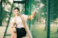Il ritratto femminile di graduazione in abito accademico sta guardando il forwa Fotografia Stock