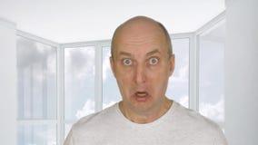 Il ritratto ha spaventato e sorpreso l'uomo che esamina la macchina fotografica con timore sulla finestra del fondo Emozione di t archivi video
