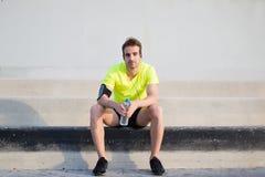 Il ritratto integrale degli sport bei equipaggia la seduta sulle scale concrete con area di spazio della copia dai lati mentre ri Fotografie Stock