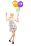 Il ritratto integrale di una tenuta femminile abbastanza bionda balloons la a Immagine Stock Libera da Diritti