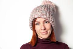 Il ritratto isolato di bella giovane ragazza della testarossa in maglione porpora e cappello tricottato rosa con il fiocchetto ha immagini stock