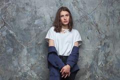Il ritratto luminoso di modo di donna teenager castana abbastanza giovane dei pantaloni a vita bassa con luminoso compone e capel Fotografia Stock