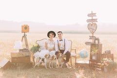 Il ritratto orizzontale adorabile delle persone appena sposate vestite annata che si siedono con i cani sul sofà circondato con immagine stock