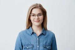 Il ritratto orizzontale di giovane sembrare piacevole felice sorridente femminile indossa la camicia del denim ed i vetri alla mo Fotografie Stock