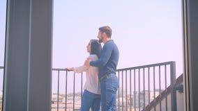 Il ritratto posteriore di giovani coppie caucasiche nell'amore abbraccia sul balcone e sul godere della vista magnifica della cit