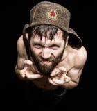Il ritratto scuro dell'uomo barbuto sinistro diabolico spaventoso con sorrisetto, fa i segni della varia mano ed esprime le emozi fotografie stock