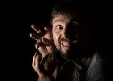Il ritratto scuro dell'uomo barbuto spaventoso con sorrisetto, esprime le emozioni differenti Gocce di acqua su un vetro, su una  Immagine Stock Libera da Diritti