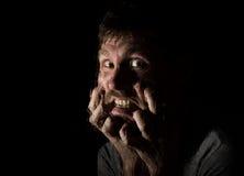 Il ritratto scuro dell'uomo barbuto spaventoso con sorrisetto, esprime le emozioni differenti Gocce di acqua su un vetro, su una  Fotografie Stock Libere da Diritti