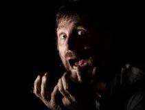 Il ritratto scuro dell'uomo barbuto spaventoso con sorrisetto, esprime le emozioni differenti Gocce di acqua su un vetro, su una  Fotografia Stock