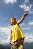 Il ritratto un bambino mostra la sua mano in avanti contro il cielo blu Immagine Stock