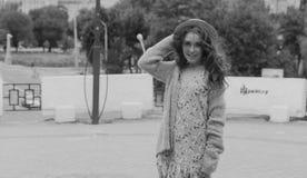 il ritratto una bella ragazza in un cappello, si siede sui residui tiene i capelli dal vento Passeggiata intorno alla città ritra fotografie stock